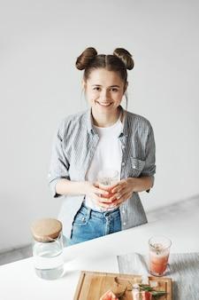 Mulher feliz que sorri guardando de vidro com o batido da desintoxicação da toranja sobre a parede branca. comida de dieta saudável.