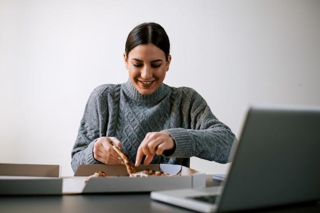 Mulher feliz que toma uma fatia de pizza ao sentar-se na frente do portátil.