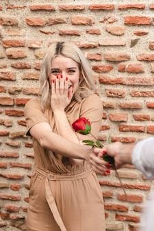 Mulher feliz, recebendo uma rosa do homem