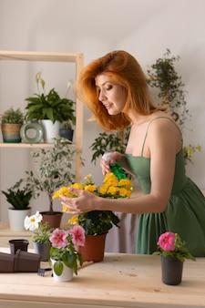 Mulher feliz regando flor de tiro médio