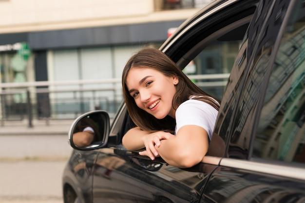 Mulher feliz relaxada na viagem de férias roadtrip de verão inclinando-se para fora da janela do carro na parede do céu azul.