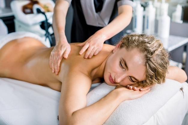 Mulher feliz relaxada que recebe massagem nas costas no spa. mulher caucasiana atraente, recebendo massagem clássica em um centro de spa