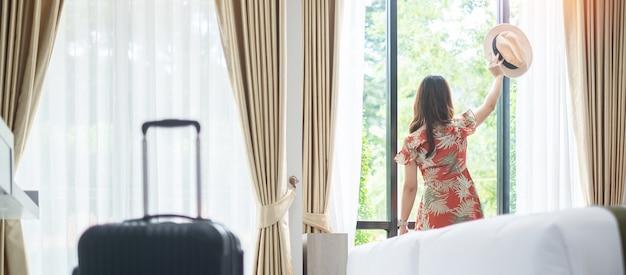 Mulher feliz relaxando perto da janela do hotel