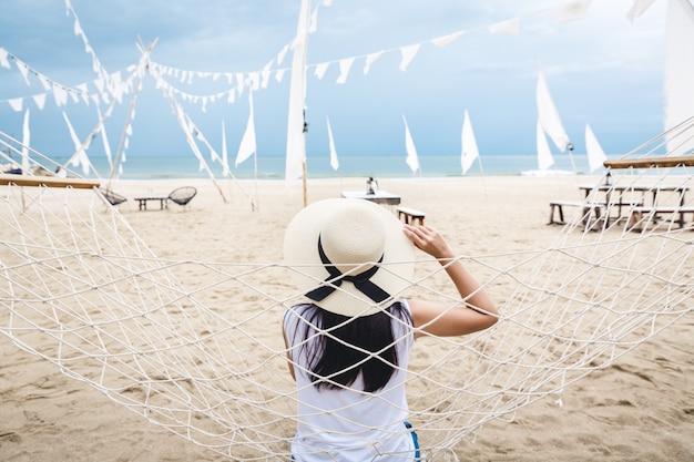 Mulher feliz relaxar na rede na praia