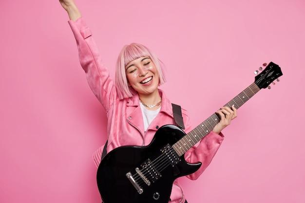 Mulher feliz, rockstar, sorrindo alegremente mantendo o braço levantado tocando guitarra elétrica usando uma jaqueta estilosa e demonstrando seus talentos no palco