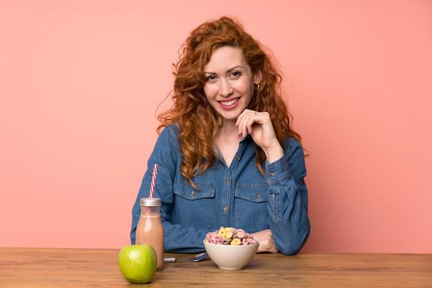 Mulher feliz ruiva tomando café da manhã