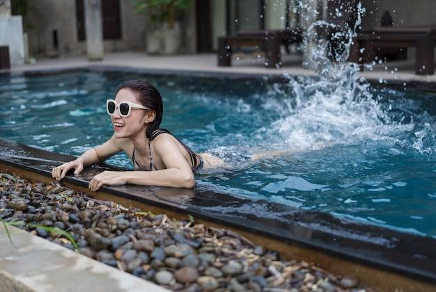 Mulher feliz, salpicos de água pela perna na piscina