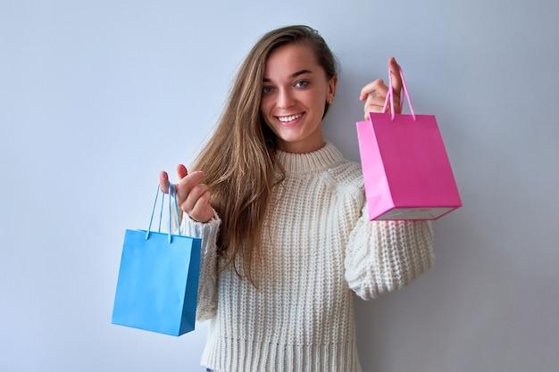 Mulher feliz satisfeita alegre viciada em compras com sacolinhas de papel colorido