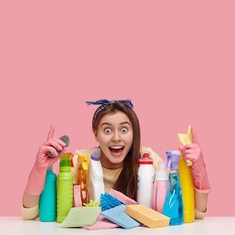 Mulher feliz satisfeita com expressão de alegria, aponta com ambos os dedos indicadores para celiling