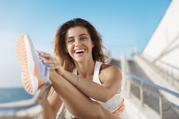 Mulher feliz, saudável, charmosa e ativa, sorrindo, rindo alegremente, esticando a perna, inclinando-se para o bar