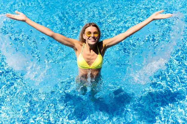 Mulher feliz se divertindo na piscina