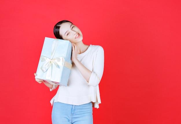 Mulher feliz se perguntando o que há dentro da caixa de presente