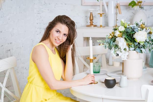 Mulher feliz se senta à mesa em um vestido amarelo, sorrindo, há um lindo buquê e um castiçal com ...
