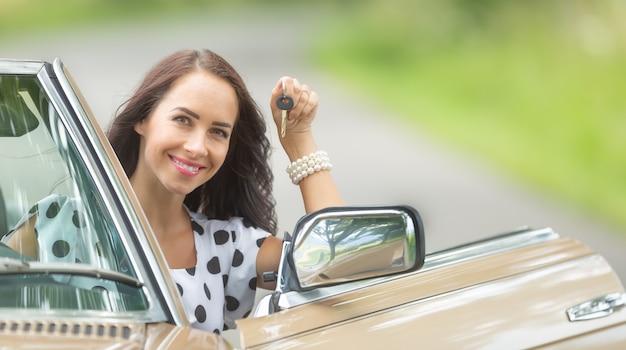 Mulher feliz se senta em um cabrio com a chave do carro na mão, usando o aluguel de automóveis.