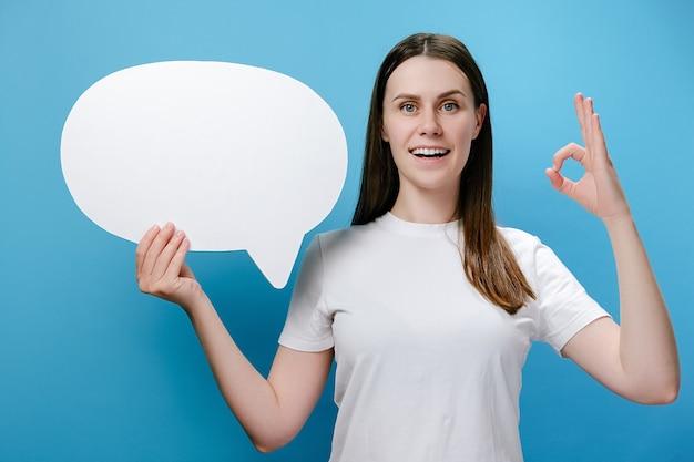 Mulher feliz segurando balão de fala e fazendo gesto de aprovação