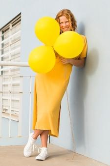 Mulher feliz, segurando balões