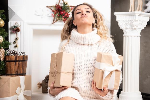 Mulher feliz segurando caixas de presente perto da lareira.