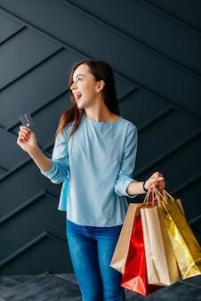 Mulher feliz segurando cartão de crédito e sacolas com compras, conceito de sexta-feira negra
