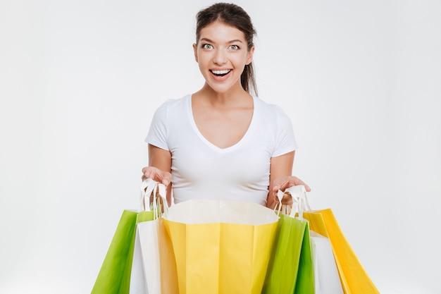 Mulher feliz segurando compras depois de fazer compras. isolado sobre parede branca