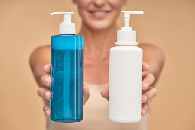 Mulher feliz segurando garrafas com produtos naturais para a pele em estúdio