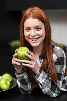 Mulher feliz, segurando maçã