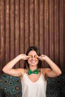 Mulher feliz segurando moedas de ouro perto dos olhos no sofá