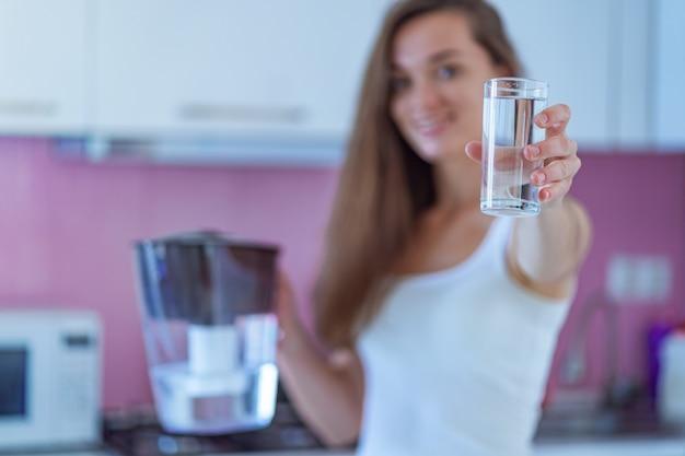 Mulher feliz, segurando o copo de água purificada na cozinha em casa