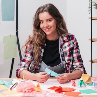 Mulher feliz, segurando, origami, ofício, olhando câmera