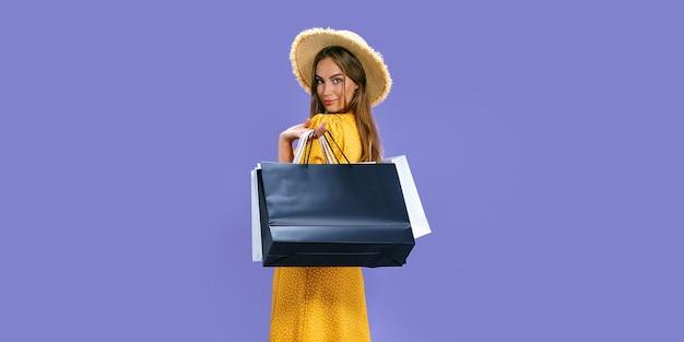 Mulher feliz segurando pacotes depois de fazer compras em descontos de fundo roxo preto sexta-feira