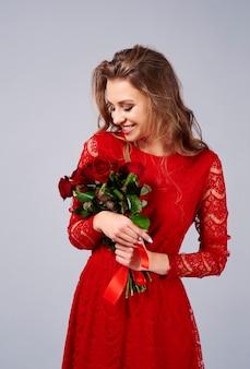 Mulher feliz segurando um buquê de rosas frescas