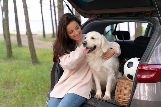 Mulher feliz segurando um cachorro com tiro médio