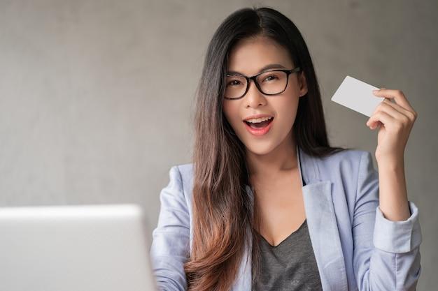 Mulher feliz segurando um cartão de crédito de modelo branco