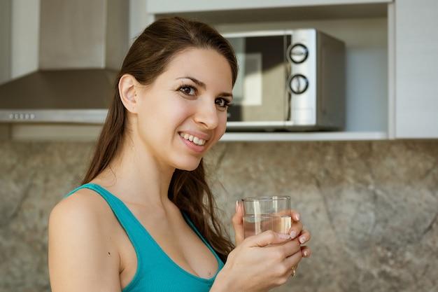Mulher feliz segurando um copo de água limpa, sorrindo na cozinha