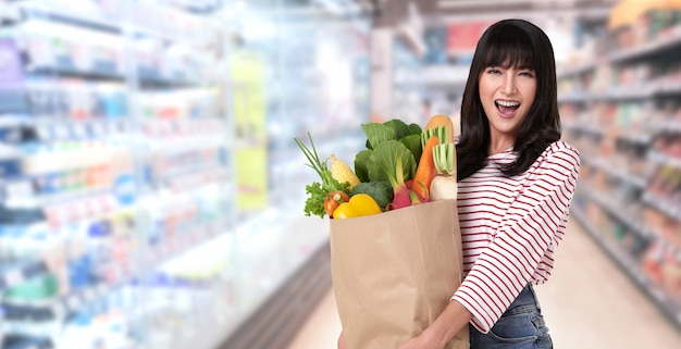 Mulher feliz segurando um saco de papel cheio de legumes frescos e baguetes no supermercado