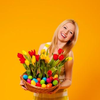 Mulher feliz segurando uma cesta com flores de primavera e ovos de páscoa