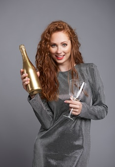 Mulher feliz segurando uma garrafa de champanhe e taça de champanhe