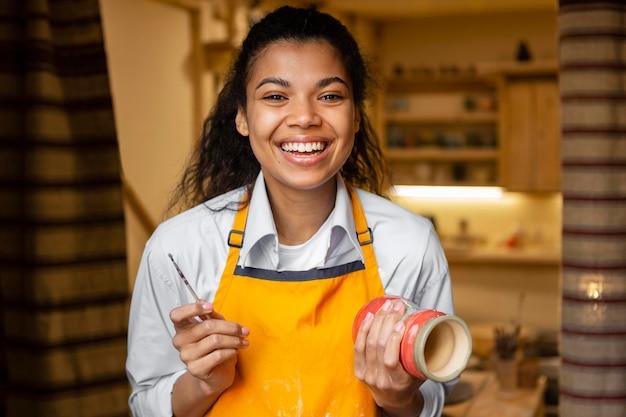 Mulher feliz segurando uma panela de barro