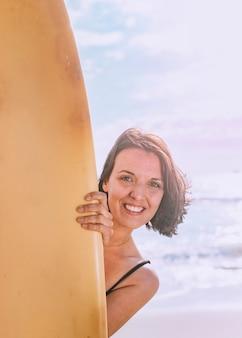 Mulher feliz segurando uma prancha de surf