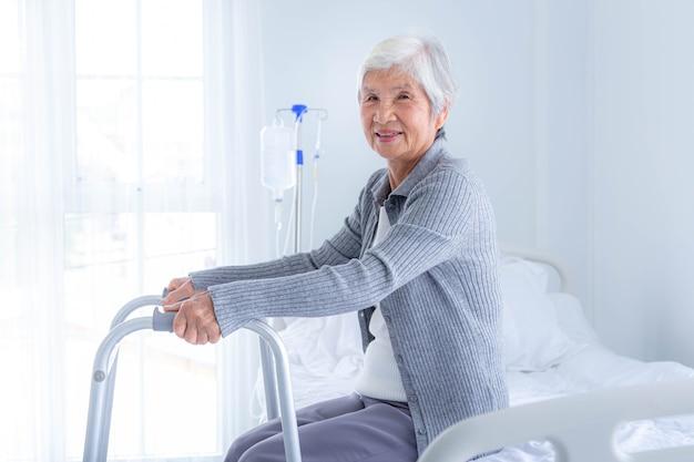 Mulher feliz sênior com andador no hospital. cuidado do paciente idoso e cuidados de saúde, conceito médico.