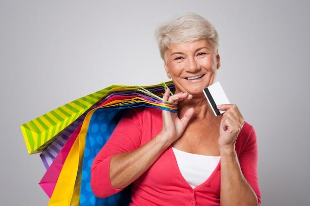 Mulher feliz sênior com cartão de crédito e sacolas de compras