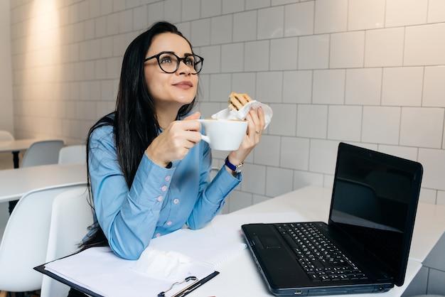 Mulher feliz sentada à mesa tomando café com sanduíche