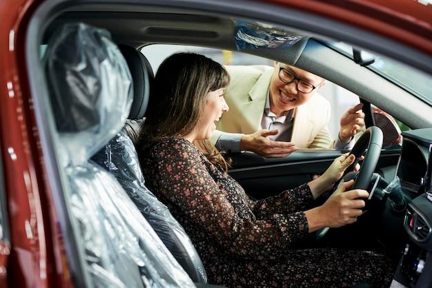 Mulher feliz sentada em um carro novo e satisfeita com sua compra com um vendedor de pé ao ar livre e sorrindo
