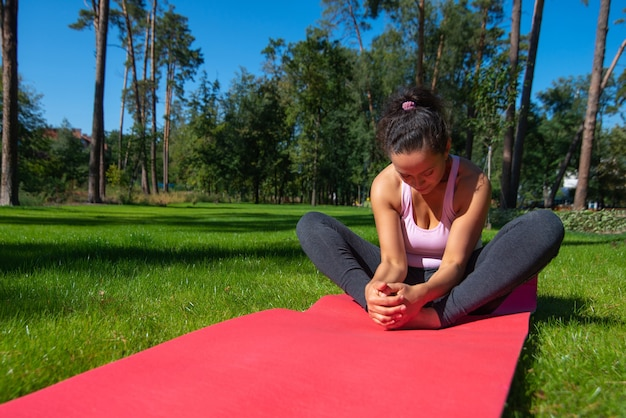 Mulher feliz sentada em uma esteira de ginástica, treinando em um dia ensolarado de verão em um fundo de uma floresta de pinheiros