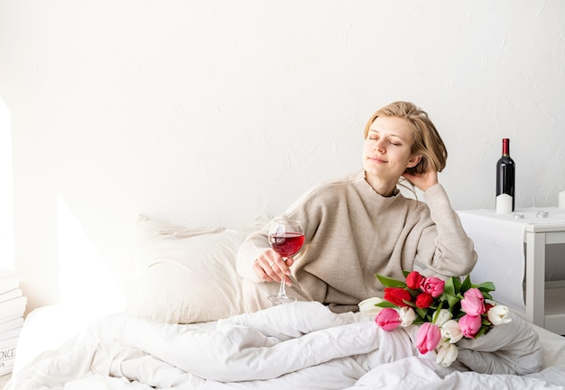 Mulher feliz sentada na cama de pijama, com o prazer de apreciar flores e uma taça de vinho tinto