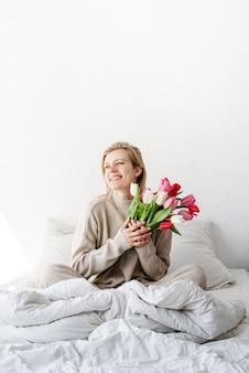 Mulher feliz sentada na cama de pijama, com prazer curtindo flores