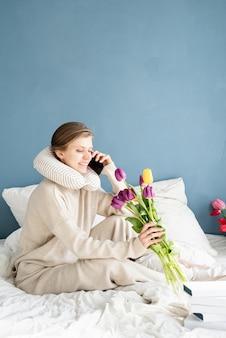 Mulher feliz sentada na cama de pijama falando ao telefone, fundo azul da parede