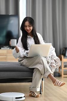 Mulher feliz sentada no sofá, trabalhando com o laptop e bebendo café enquanto o robô aspira o chão em casa