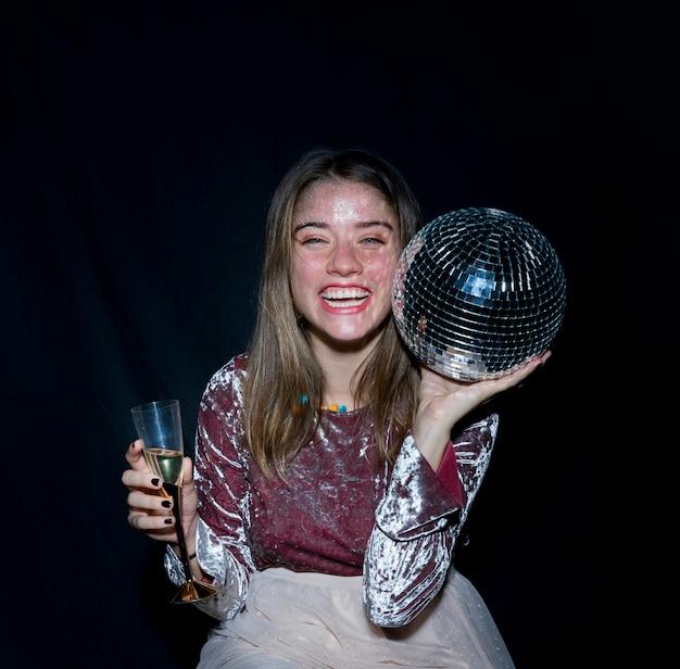 Mulher feliz sentado com bola de discoteca na mão