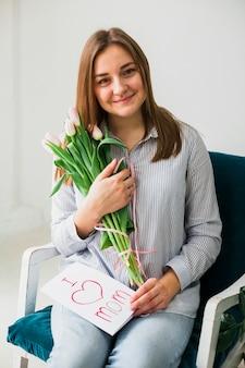 Mulher feliz sentado com cartão e flores
