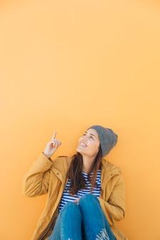 Mulher feliz sentado contra o pano de fundo amarelo apontando para cima